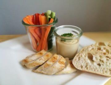 Gegrilltes Fleisch mit Hummus, Fladenbrot und Gemüsesticks